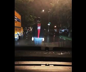 車の進路を邪魔する男