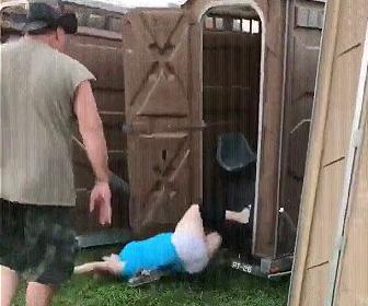 仮設トイレから転げ落ちる女性