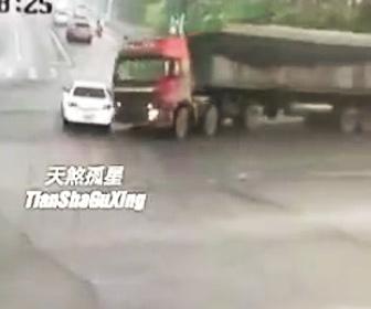 トラック積み荷の砂に潰される車