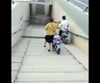 スクーターを押し階段を下る