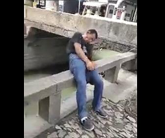 橋の欄干に座り寝ている男性が川に落下