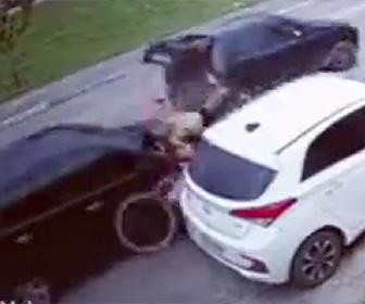 車に挟まれ自転車に乗る少年が轢かれる