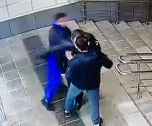 タバコを吸う男が後ろから警備員に殴りかかる。