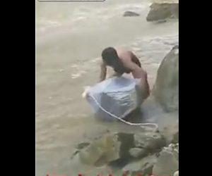 妻をビニール袋に入れ激流を渡る夫