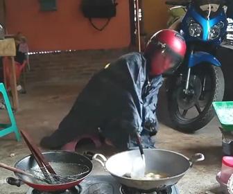 【動画】飛び散る油を避けるため、フルフェイスにカッパを付けて料理をする