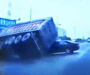 【動画】砂を積んだ大型トラックが左折するが横転。車が下敷きになってしまう