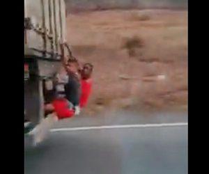 高速道路を猛スピードで走るトラック。少年2人がトラックの後ろにしがみ付いている衝撃映像