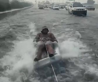 【衝撃】洪水で浸水した車道をエアーマットに乗った男性が車に引っ張られ走る衝撃映像