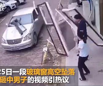 【衝撃】建物から窓が落下し道に止まっている車に激突する衝撃映像