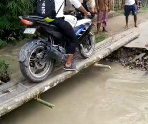 【衝撃】濁流により道が寸断され、細い木の橋をバイクが慎重に渡ろうとするが…