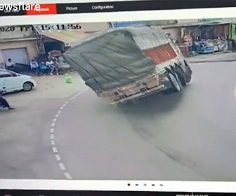 【事故】大量の荷物を積んだトラックがカーブで横転。店先にいた人達が必死に逃げる衝撃事故映像