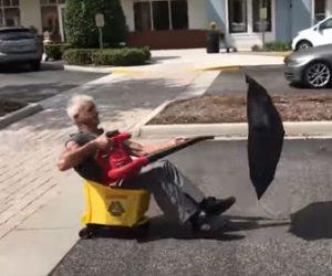 【衝撃】清掃作業員がキャスター付きのバケツに座り、傘とブロワーで猛スピードで走る衝撃映像