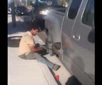 【衝撃】駐車車両のタイヤを盗もうとする男。運転手が泥棒を見つけるが…