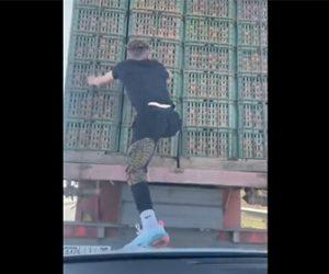 【衝撃】前を走るトラックに飛び移り、積み荷のオレンジを盗んで車に帰ってくる衝撃映像