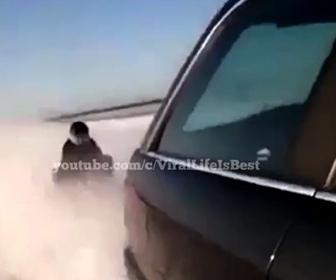 【衝撃】男性がソリに乗り、時速90マイル(145キロ)で走る車に引っ張らる衝撃映像