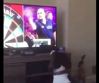 【動物】テレビ画面の中で男性が投げるダーツの矢を犬が取りに行く