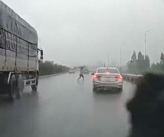 【事故】高速道路を傘をさした女性が渡ろうとするが、車にはね飛ばされてしまう衝撃映像
