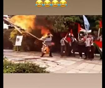 【衝撃】大きなフラッグに火を付けて燃やそうとするが、風にあおられ火がフラッグを持つ男性に…