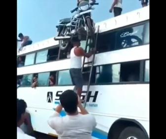 【衝撃】バイクを頭に乗せて梯子を登りバスにバイクを乗せる男性が凄い