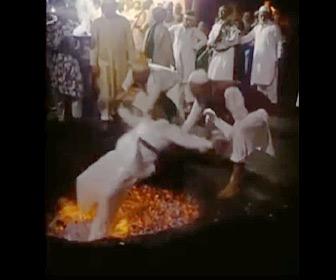 【動画】儀式で2人の男性に抱えられ、男性が真っ赤に燃えた炭の上に立とうとするが…
