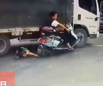 【動画】親子が2人乗りするバイクが車道の穴でコントロールを失いトラックに…
