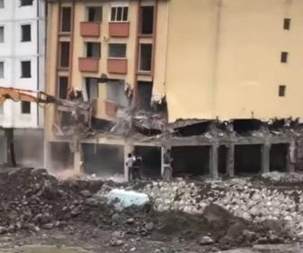 【動画】ショベルカーで建物を解体するが突然崩壊してしまい、そばにいた人達が必死に逃げる